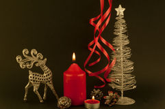 Christmas decoration. Deer, red candles, cones with glitter, ribbon packing on a black background stock photos