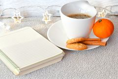 Winter weekend. Christmas decoration Delicious home made    cinnamon cookies mandarin, ,cup of coffee  on balcony in a snowy day Lazy winter weekend with a book Stock Photos