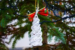 Christmas decoration element on branch. Christmas decoration element on outdoor Christmas tree branch closeup shot royalty free stock photography