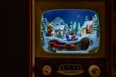 Christmas decoration. An entire village in a small antique TV, with the train and people on the streets royalty free stock photo