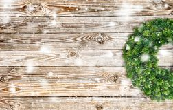 Christmas decoration wreath wooden background snow. Christmas decoration evergreen wreath on rustic wooden texture. Vintage background with falling snow effect stock images