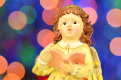 Christmas decoration, figure of little angel singing carols. Against bokeh background royalty free stock image