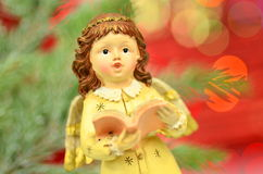 Christmas decoration, figure of little angel singing carols. Against bokeh background royalty free stock photography