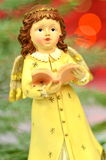Christmas decoration, figure of little angel singing carols. Against bokeh background royalty free stock photos