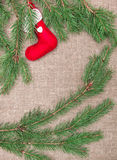 Christmas decoration with fir branches and red sock on burlap Stock Photos