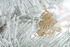 Christmas decoration on fir tree. Metallic golden decorative toy in shape of a fir-tree hanging on rimed Christmas tree branch Royalty Free Stock Images