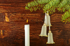 Christmas decoration. Fir-tree, bells and candle Royalty Free Stock Photos