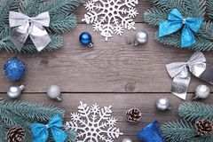 Christmas decoration. Fir-tree branch with balls, bumps, snowflake and bows on a grey background. Christmas decoration. Fir-tree branch with balls, bumps stock image