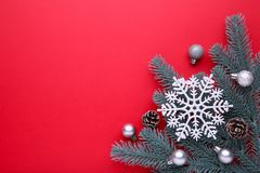 Christmas decoration. Fir-tree branch with balls, bumps, snowflake on a red background royalty free stock photo
