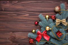 Christmas decoration. Fir-tree branch with balls, gifts and bows on a brown background stock image