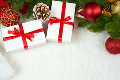 Christmas decoration on fir tree branch closeup, gifts, xmas ball, cone and other object on white blank space fur, holiday concept Stock Image