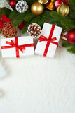 Christmas decoration on fir tree branch closeup, gifts, xmas ball, cone and other object on white blank space fur, holiday concept Royalty Free Stock Images