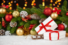 Christmas decoration on fir tree branch closeup, wooden sledge toy, gifts, xmas ball, cone and other object on white blank space f Royalty Free Stock Photo