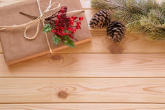 Christmas decoration - fir tree branch, gift and holly berry Royalty Free Stock Photos
