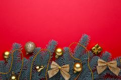 Christmas decoration. Fir-tree branch with gold balls, little gifts and bows on a red background stock photography