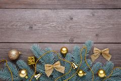 Christmas decoration. Fir-tree branch with red balls, little gifts and bows on grey royalty free stock photos