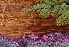 Christmas decoration. Fir-tree, tinsel and wooden background. Stock Photos