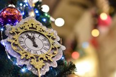 Christmas decoration in the form of a small clock. With a pendulum on a festive spruce on the background of bright bokeh lights and highlights stock photo