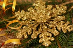 Christmas decoration in the form of a snowflake with a serpentine gold color on the background of Christmas branches and burlap. stock image