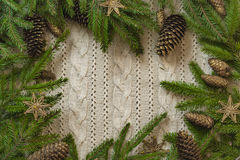 Christmas decoration frame with knitted wool background and fir. Space for text Stock Photos