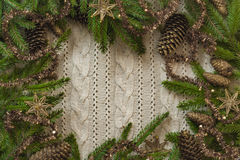 Christmas decoration frame with knitted wool background and fir. Space for text Royalty Free Stock Photography