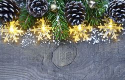 Christmas decoration with garland lights,pine cones and fir tree on old wooden background. Christmas border.Winter holidays concep Royalty Free Stock Photo