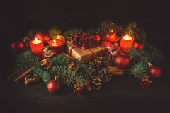 Christmas decoration with gift box, baubles,fir tree and burning red candles Royalty Free Stock Photography