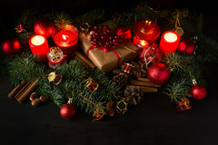 Christmas decoration with gift box, baubles,fir tree and burning red candles Stock Photography