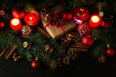 Christmas decoration with gift box, baubles,fir tree and burning red candles Royalty Free Stock Images
