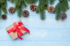 Christmas decoration, gift box and pine tree branches on wooden background, preparation for holiday concept, Happy New Year and Xm. As Holidays. Top view and stock photography