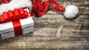 Christmas decoration. Gift box red ribbon bow falling snow Stock Photography