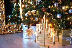 Beautiful Christmas interior. A Christmas tree with gold ornaments, boxes with gifts, and a candelabrum with burning Royalty Free Stock Photography