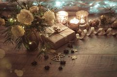 Christmas decoration. Gift, candles, lights, golden balls on a wooden rustic table. Composition of pine branches and. Christmas decoration. Gift, candles, lights Stock Image