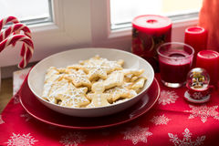 Christmas decoration: gingerbread cookies, candies, toys and burning red candles Stock Photos
