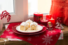 Christmas decoration: gingerbread houses, candies, toys and burning red candles Stock Photo