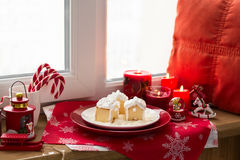 Christmas decoration: gingerbread houses, candies, toys and burning red candles Stock Photos
