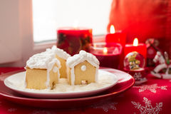 Christmas decoration: gingerbread houses, candies, toys and burning red candles Royalty Free Stock Photo