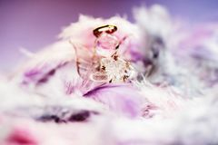 Christmas decoration, glass angel,feather,blurry. Christmas decoration with blurred feather and glass angel protector, violet,pink,blue,gold,white Stock Photography