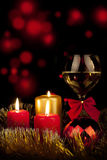 Christmas decoration glass with champagne and burning candles. Red Royalty Free Stock Photo