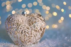 Glass heart on a snow and toned blurred color background of glittering bokeh with glowing lights. Christmas decoration. Copy space stock images