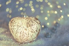 Glass heart on a snow and toned blurred blue background of glittering bokeh with yellow lights. Christmas decoration. Copy space stock image