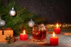 Christmas decoration with glass of whiskey or cognac, christmas candles, tree and gift box on a sparkling background Royalty Free Stock Photo