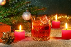 Christmas decoration with glass of whiskey or cognac, christmas candles, tree and gift box on a sparkling background Royalty Free Stock Images