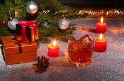 Christmas decoration with glass of whiskey or cognac, christmas candles, tree and gift box on a sparkling background Stock Photography