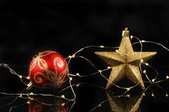 Star bauble and lights. Christmas decoration, gold glitter star and red bauble with fairy lights against a black background royalty free stock photography
