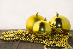 Christmas decorations, golden and rustic. Christmas decoration with golden beads and golden shiny balls on a wooden base Stock Photos