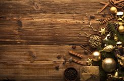 Christmas theme. Christmas decoration in golden and brownish aesthetics with presents in boxes, golden baubles, christmas spices all on a rustic wooden Stock Photography