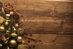 Christmas theme. Christmas decoration in golden and brownish aesthetics with presents in boxes, golden baubles, christmas spices all on a rustic wooden Stock Photos