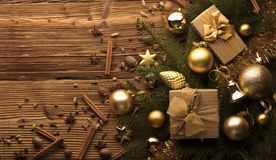 Christmas theme. Christmas decoration in golden and brownish aesthetics with presents in boxes, golden baubles, christmas spices all on a rustic wooden Royalty Free Stock Images