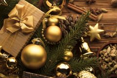 Christmas theme. Christmas decoration in golden and brownish aesthetics with presents in boxes, golden baubles, christmas spices all on a rustic wooden Royalty Free Stock Photos